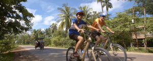 Adam and his wife Marie riding in Cambodia; courtesy Grasshopper Adventures