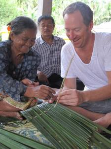 Making reed rooftop shingles at Baan Talay Nok fishing village with Andaman Discoveries homestay experience