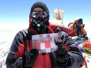 Billi atop Everest with a picture of her family