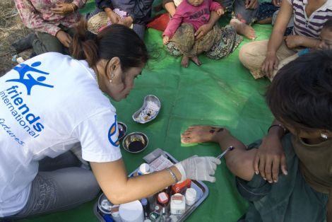 A doctor working for friends International cleans an injury sustained by a child worker at the Siem Reap tip