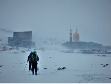 John and Kathleen Skiing past Saheb al Zaman Mosque on slopes of Damavand- Skiing in Iran on Talk Travel Asia podcast